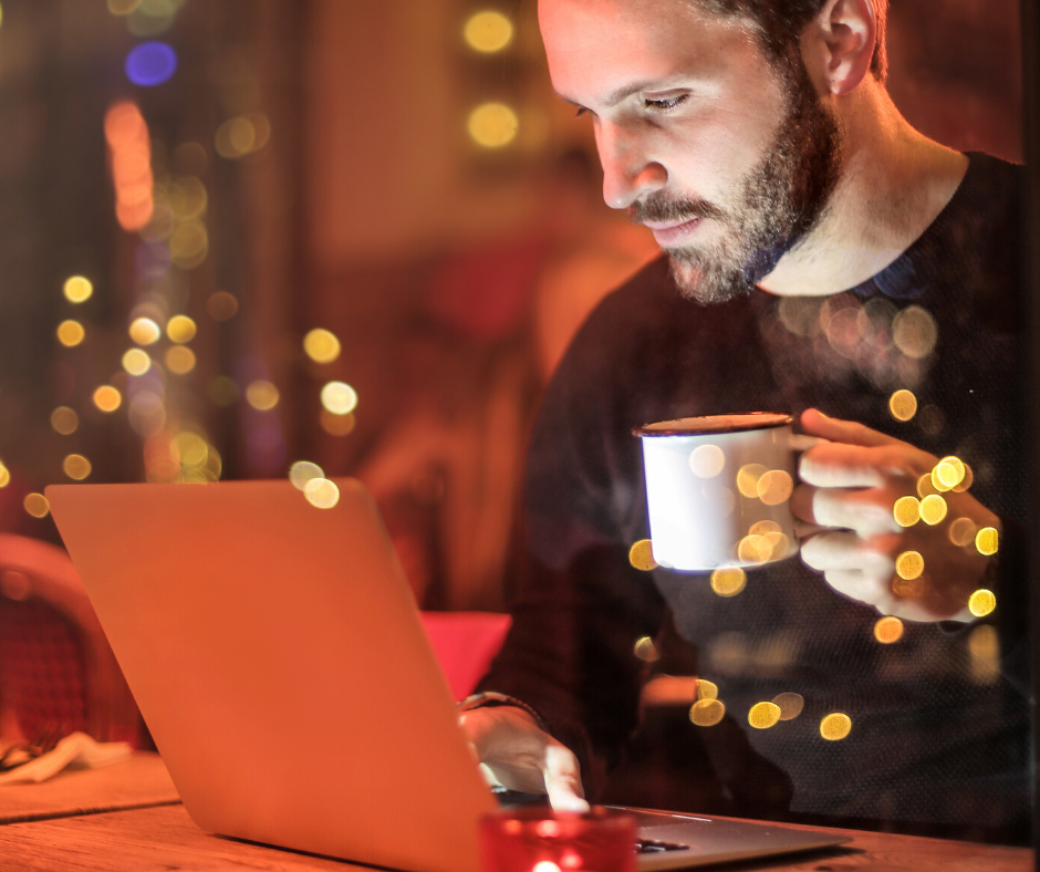 Man drinking coffee and using laptop in the evening